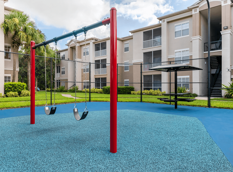 Swingset and Picnic Table on Blue Rubber Flooring with Building Exteriors in the Background
