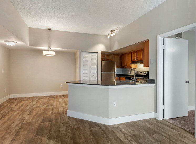 Dining room with hardwood style flooring, pass through bar to kitchen with wood cabinets