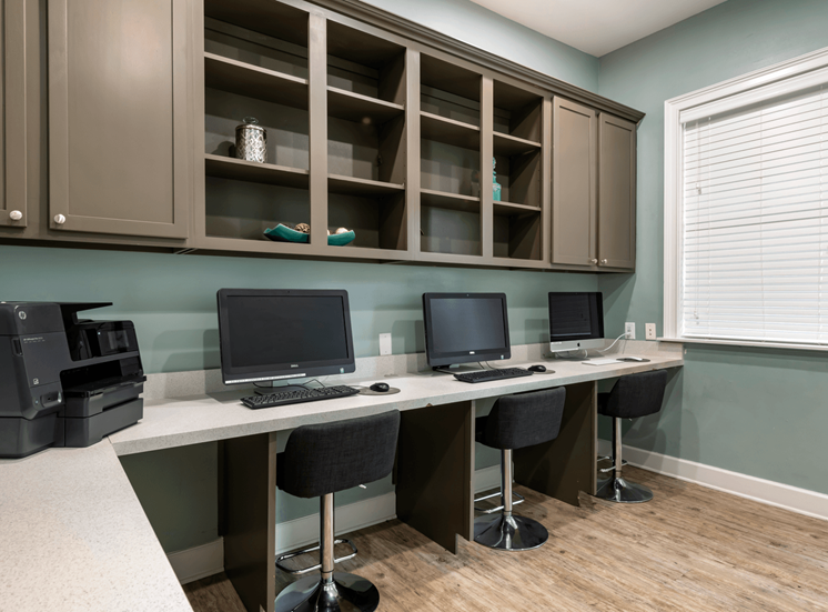 Business center with three computer, a printer and built in shelves