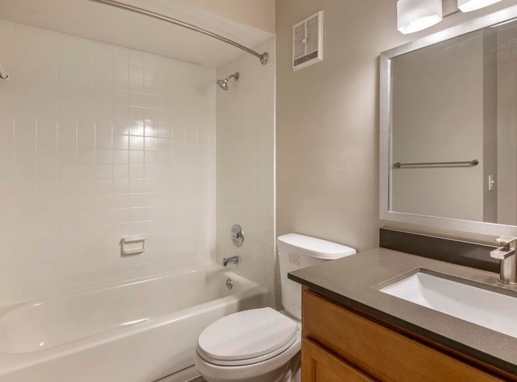 Bathroom with granite countertops, toilet, white shower tiles in the standup shower with bathtub and towel bars.