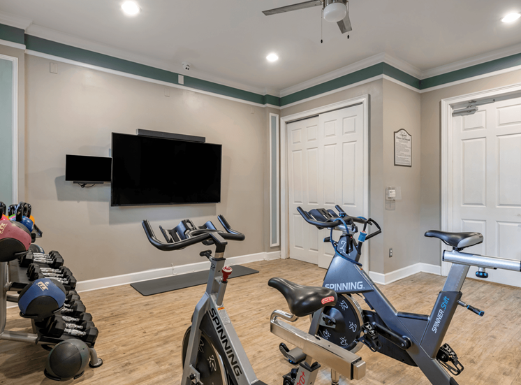 Bright Fitness Center with Exercise Equipment and Mounted TVs
