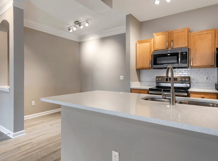 Kitchen with Wood Cabinets, Stainless Steel Appliances and White Counters