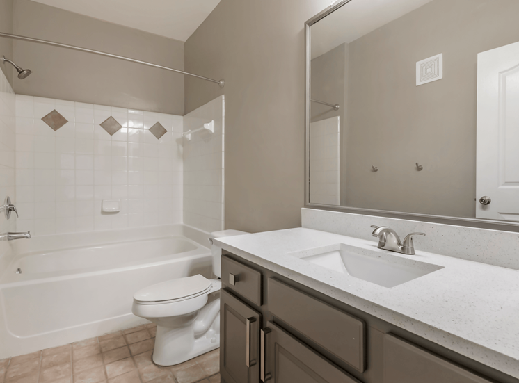 BAthroom with White Counters, Grey Cabinets and Tiled Shower with Bathtub