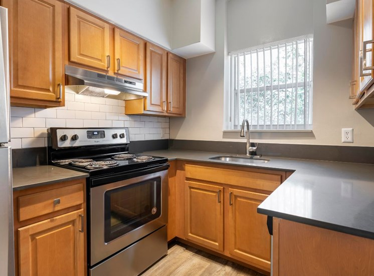 Kitchen with Stainless Steel Appliances, brown cabinets, hardwood style flooring and window over the kitchen sink