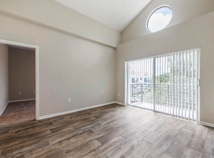 Livingroom with hardwood style flooring, vaulted ceilings, two tone paint, sliding patio door to balcony