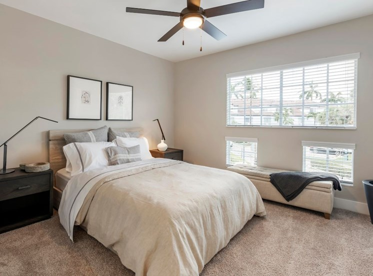 Spacious bedroom with carpet flooring, multi-speed ceiling fan, two side dressers with table lamps, and windows for natural lighting