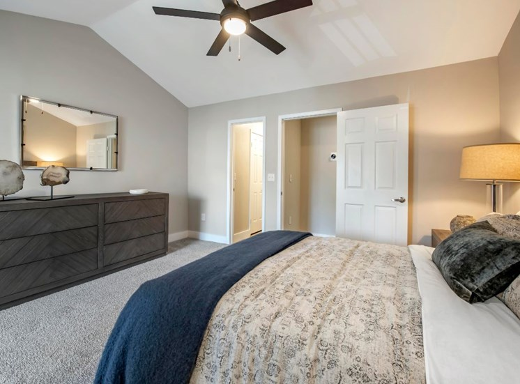 Spacious bedroom with large dresser, mirrored accent walls, carpet flooring, multi-speed ceiling fan, walk-in closet, and side dresser with lamp