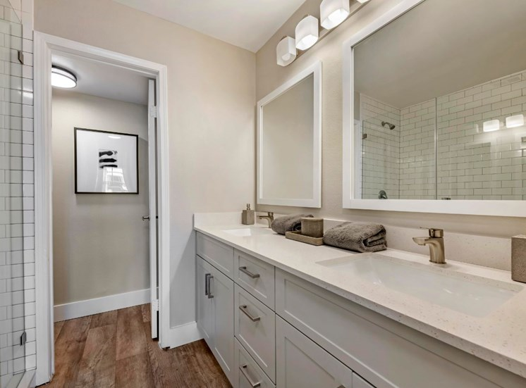 Bathroom with hardwood style flooring, stand up shower, double vanity sink, and vanity lighting with two large mirrors