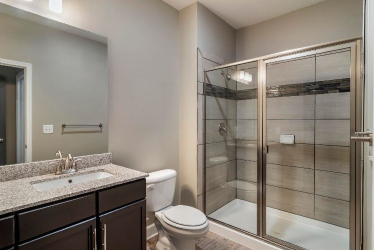 Bathroom with Brown Cabinets Grey Counters and Walkin Glass Shower