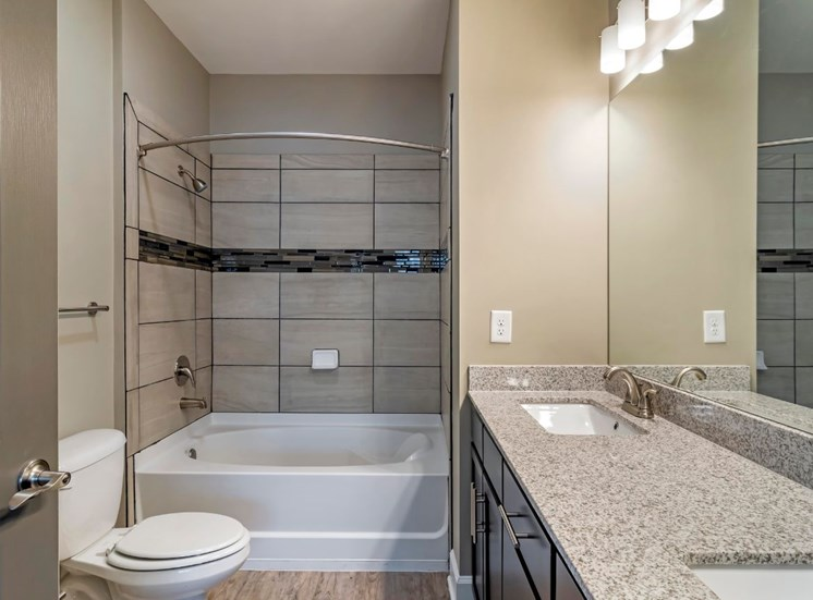 Bathroom with Grey Counters and Dark Brown Cabinets with Tiled Shower