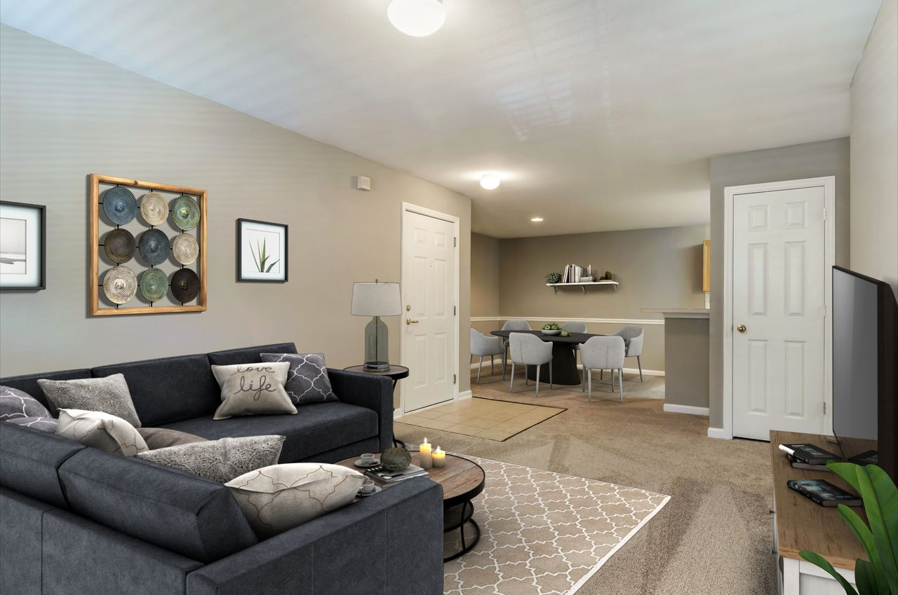 Carpeted Living Room Next to Dining Room with Virtually Staged Couch, Coffee Table, Area Rug and Dining Table