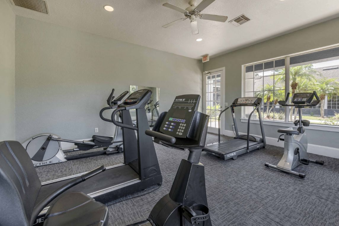 Bright Fitness Center with WIndows and Exercise Equipment And Ceiling Fan