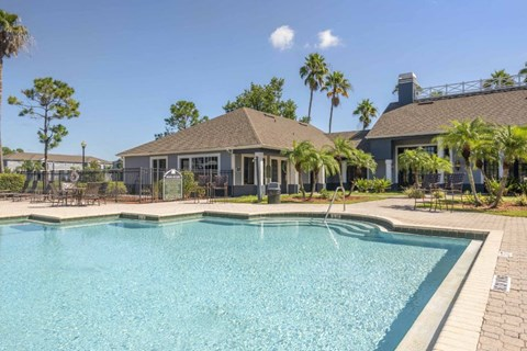 Leasing Office Exterior with Swimming Pool and Sun Deck with Lounge Chairs with Trees and Building Exterior in the Background