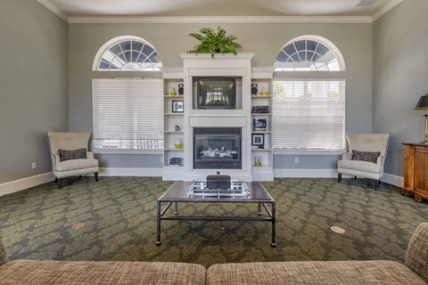 Clubhouse Seating Area with Large Windows Metal Coffee Table White Arm Chairs on either side of Fireplace with Decorative Plant Above TV with Decorative Items on Shelves Surrounding Fireplace