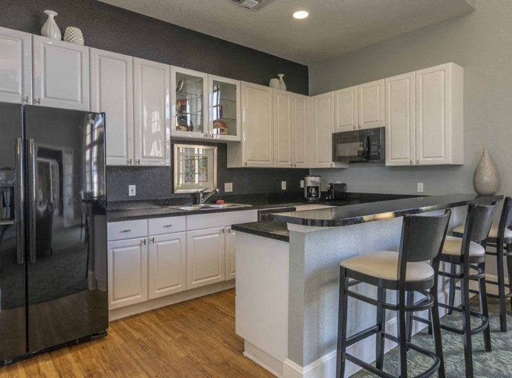 Clubhouse  Kitchen With Black Appliances and Counters White Cabinets Hardwood Floors and Bar Stools
