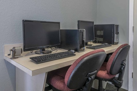 Beige Desk with a Hand Crank Pencil Sharpener Two Computers and Two Blank and Maroon Rolling Chairs