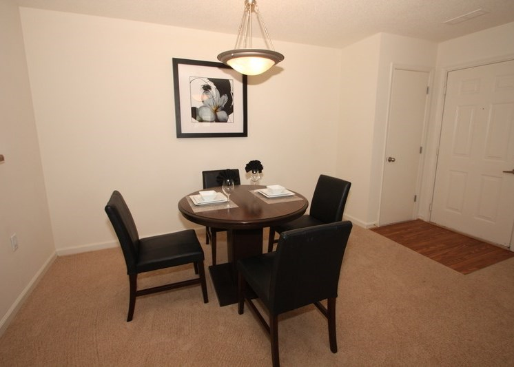 Dining room with round table and four chairs, light above table, and framed artwork in the background