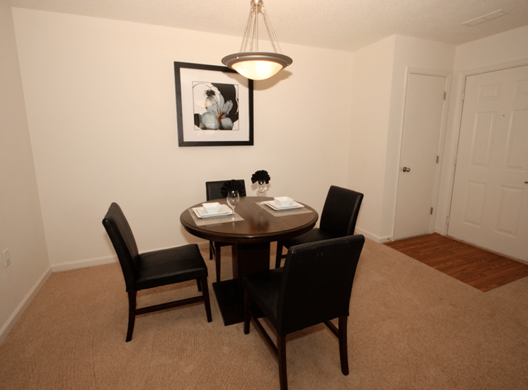 Dining room with carpet flooring, pendant lighting, and wall art