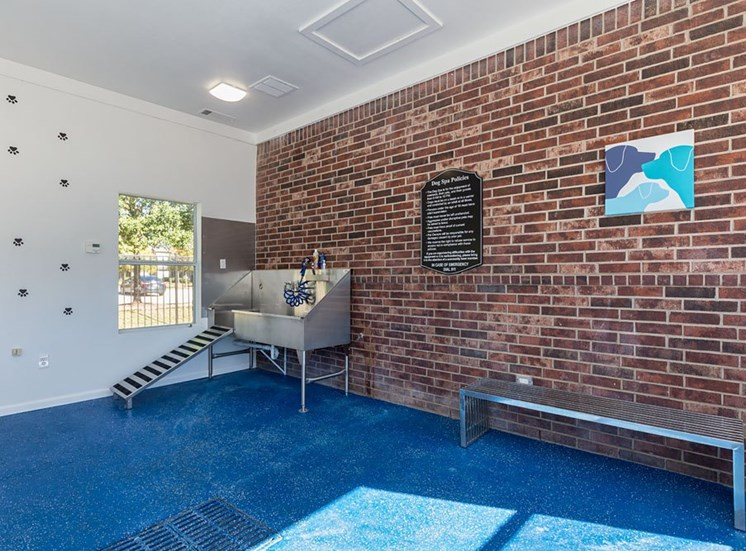 Dog Grooming Station with Metal Bath and Metal Bench Against Brick Wall