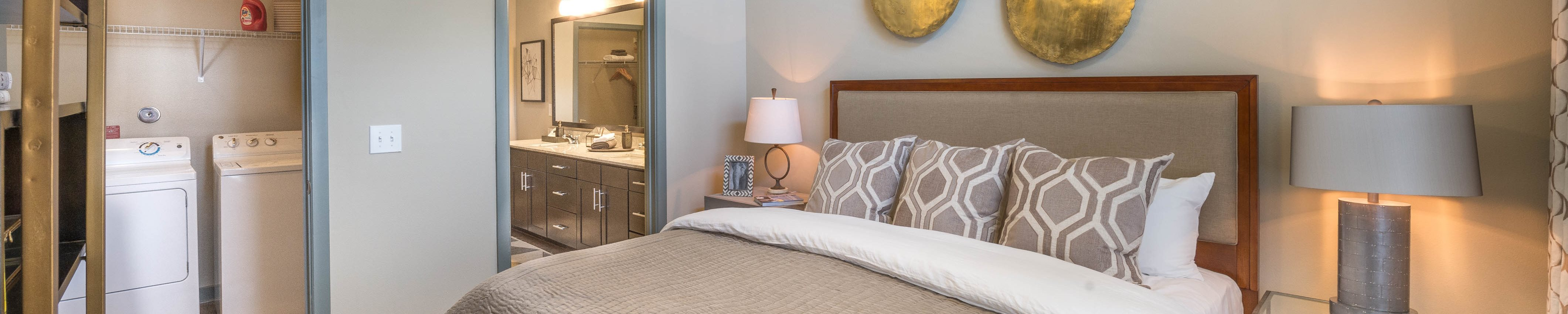 Bedroom with gold decorations on the wall, en suite bathroom, and night stands with lamps