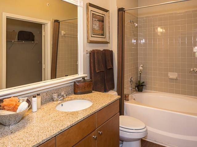 Model Bathroom with Wood Cabinets Tan Counters and Decorations