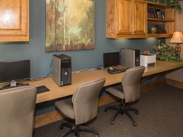Business Center with Computers and a Printer on Tan Counter with Rolling Chairs Below Wood Cabinets