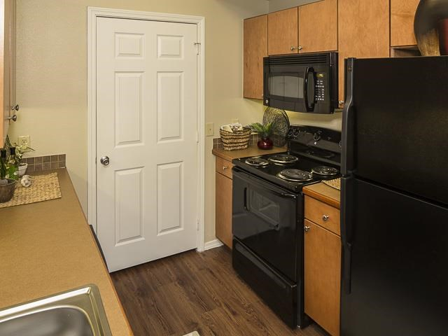 Fully Equipped Model Kitchen with Black Appliances Wood Cabinets and Tan Counters