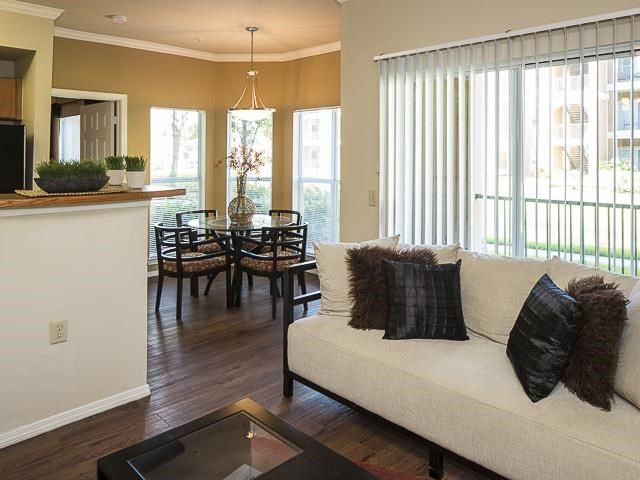 Model Living Room with White Couch Hardwood Style Flooring and Dining Table in the Background