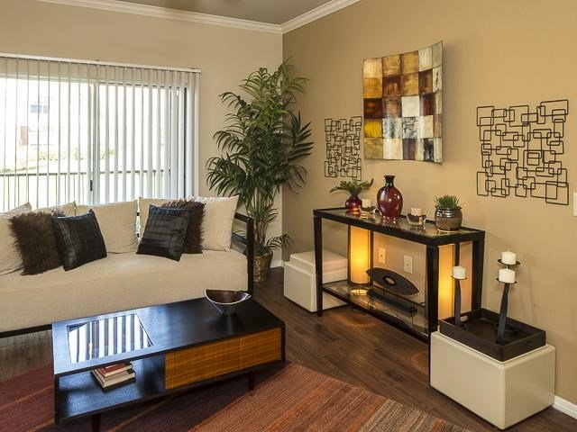 Model Living Room with White Couch Coffee Table Buffet Table and Decorations and Hardwood Style Flooring