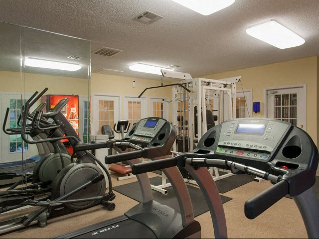 Fitness center wither two treadmills, black rugs, and bicycle machine