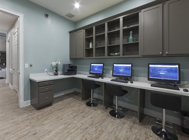 Business Center with Computers and a Printer on Grey Counter with Stools Below Grey Cabinets