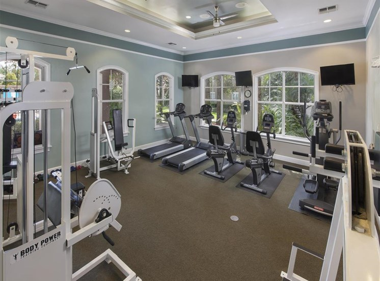 Bright Fitness Center with WIndows and Exercise Equipment and Mounted TVs