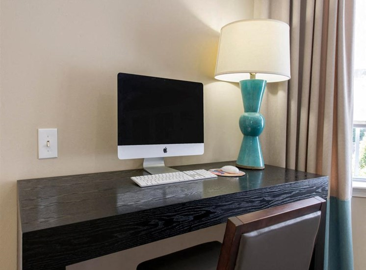 Business Center Apple Computer on Desk Next to Lamp