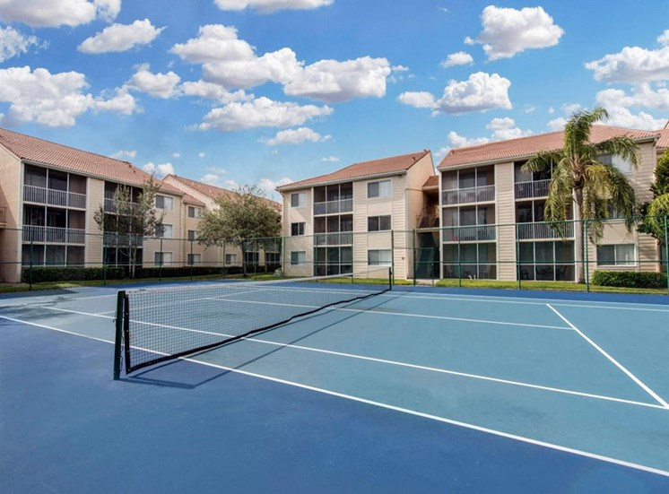 Fenced in Tennis Courts Surrounded by Apartment Building Exteriors