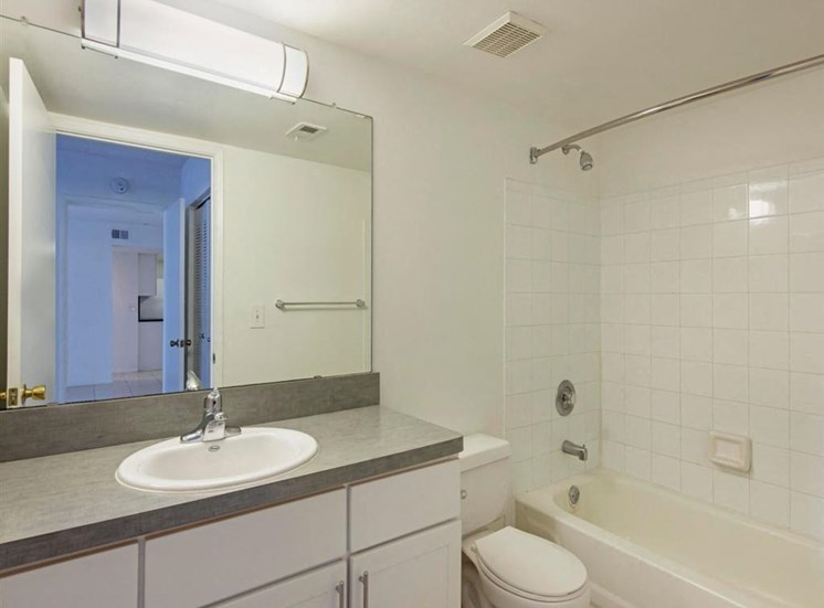 Bathroom with Grey Counters, White Cabinets and Tiled SHower with Bathtub