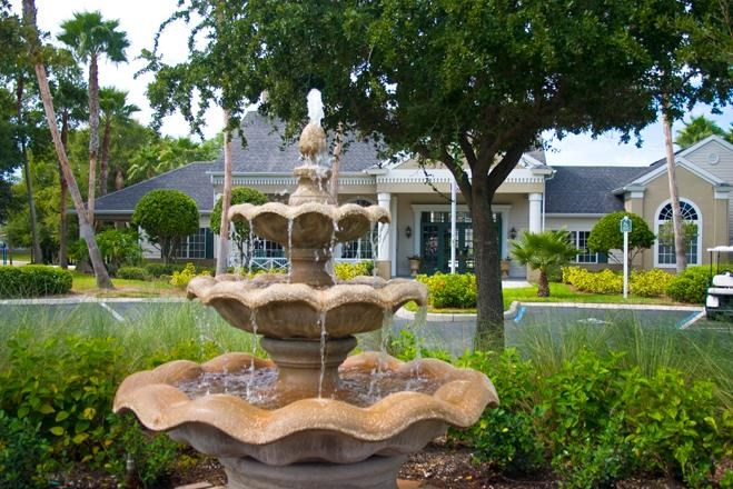 Water Fountain In Shrubs with a Tree in the Background as Well as The leasing Office and Paking Lot