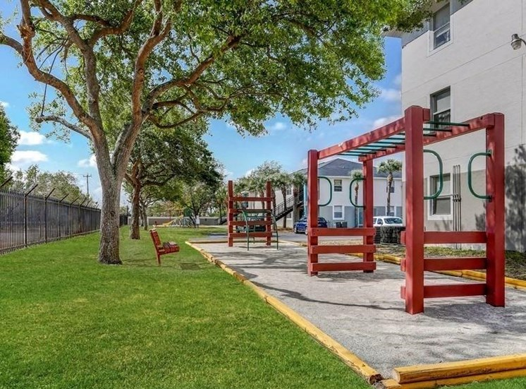 Playground in courtyard with trees and grass