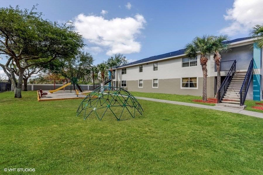 Playground in courtyard with grass and building exterior