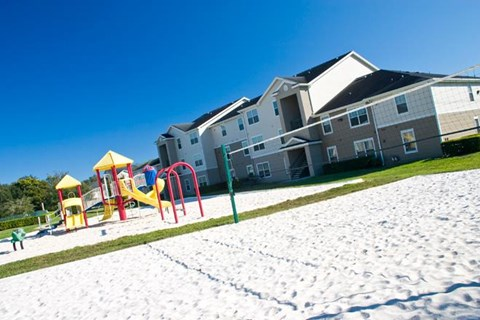 Sand Volleyball Court Next to Colorful Playground on Sand Separated by Grass with Building Exterior in the Background