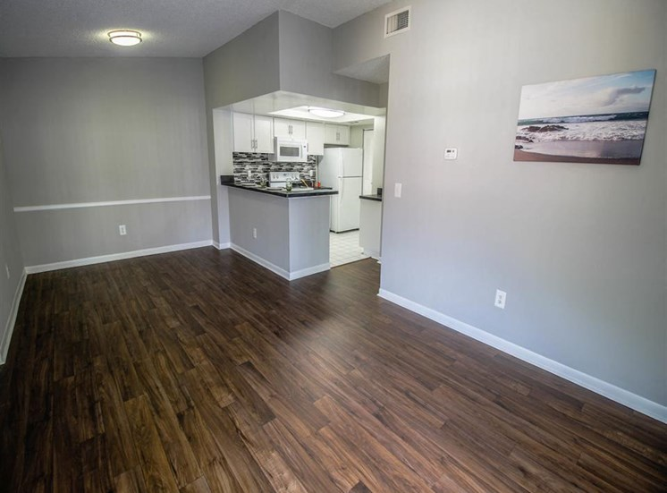 Open Floor Plan with Breakfast Bar off Kitchen and Hardwood Style Flooring