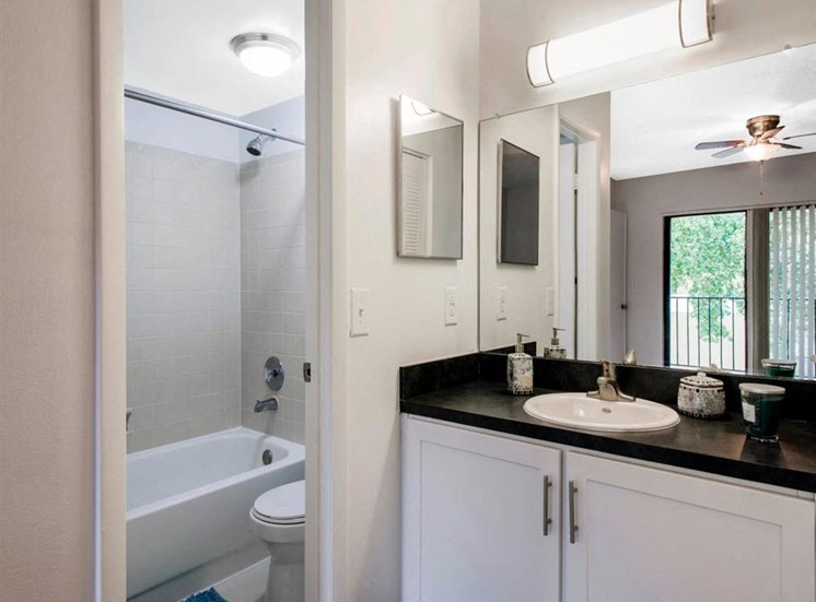 Bathroom with Separate Vanity, Black Counters, White Cabinets, and Bathtub in Seperate Room