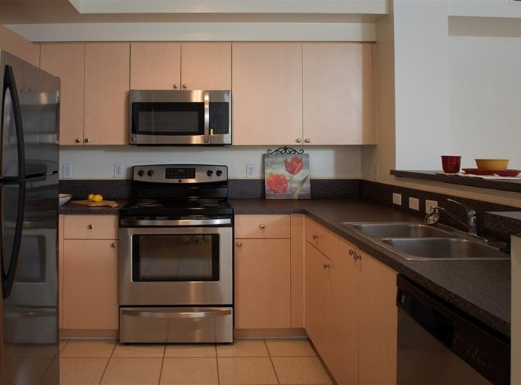 Fully equipped kitchen with stainless steel appliances, brown cabinets, pass through kitchen bar and tile flooring