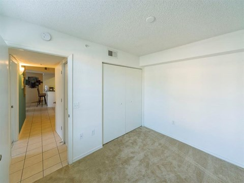 Bedroom with Sliding Closet and Hallway Leading to the Kitchen