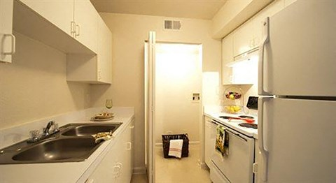 Kitchen with White Cabinets and Appliances with White Counters Double Sink and Utility Closet