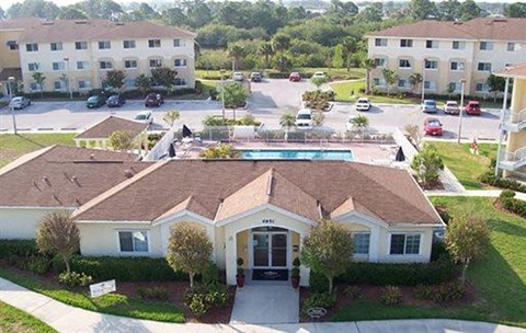 Aerial View of Leasing Office Exterior with Swimming Pool and Sun Deck with Lounge Chairs with Trees Parking Lot and Building Exteriors in the Background