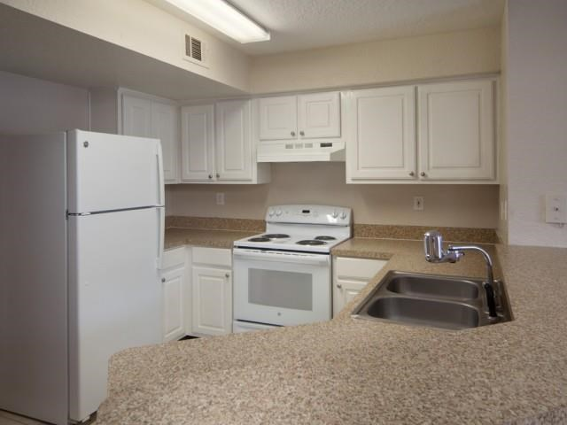 Kitchen with White Cabinets Beige Counters Double Sink and White Appliances