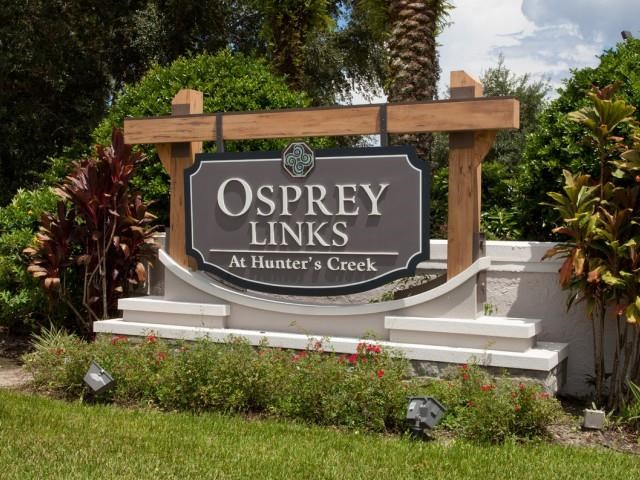 Community Entrance Sign on Grass with Decorative Plants in Front of Tree Line