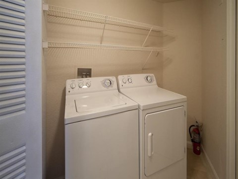 Utility Closet with White Wire Shelf Over Full Sized Washer and Dryer
