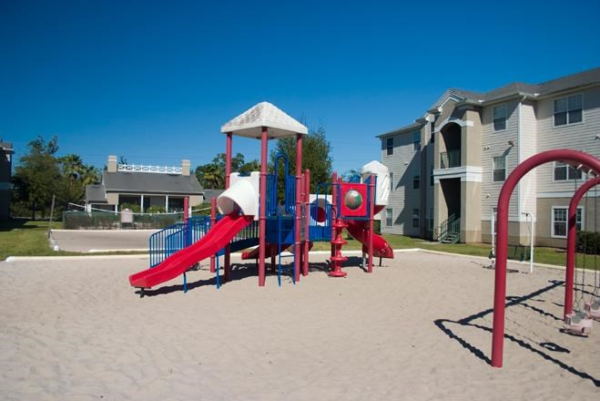 Colorful Playground on Sand with Building Exteriors in the Background