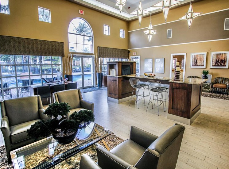 Leasing Office Interior with Armchairs Around Coffee Table, Leasing Desk Next to Window and Coffee Bar with Stools